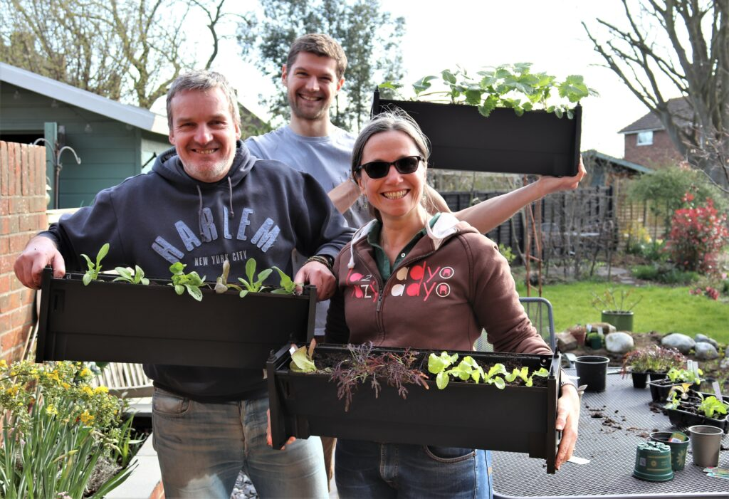Three happy PlantBox growers show their planted troughs
